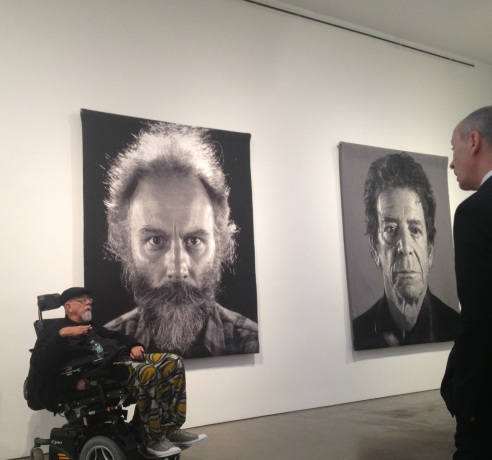 Chuck Close in 2012 with Tapestry portraits of Lucas Samaras (left) and Lou Reed (right).