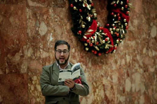 "A man reads out load from the book ""Night"" by Elie Wiesel while standing in the lobby at Trump Tower in New York"